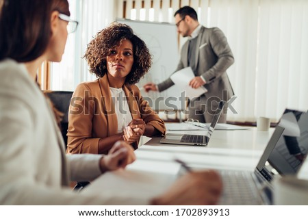 Female colleagues consulting at the meeting
