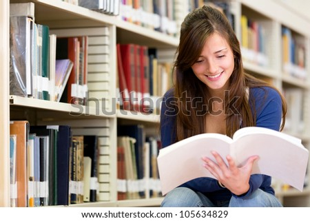 Female college student at the library reading a book
