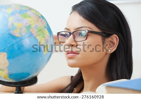 Female college student looking at a globe