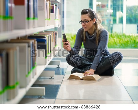 female college student sitting on floor in library, typing on mobile phone. Horizontal shape, front view, full length, copy space