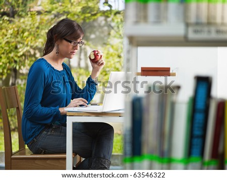 female college student studying in library and eating red apple. Horizontal shape, side view, three quarter length