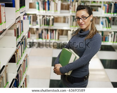female college student with books standing near shelf in library. Horizontal shape, side view, waist up, copy space