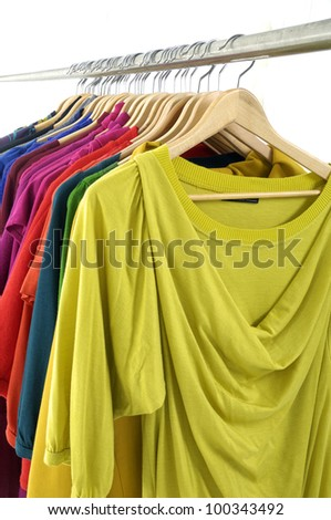 female colorful shirt clothing hanging on hangers