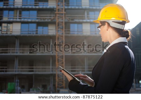 Female construction engineer/architect using tablet computer at construction site