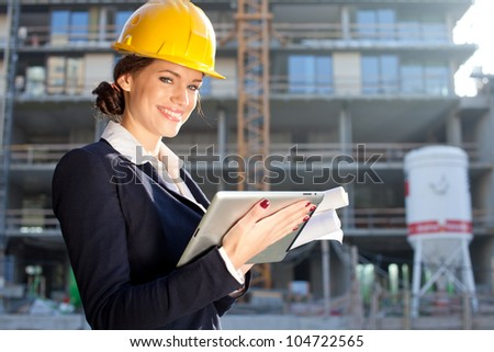 Female construction engineer / architect with a tablet computer at a construction site