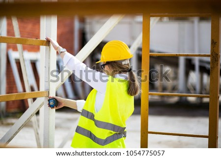 Female construction engineer or architect in hard hat using measure tape  #1054775057