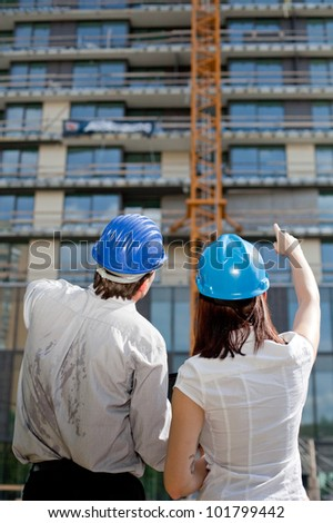Female construction engineer pointing on a building at construction site. Selective focus.