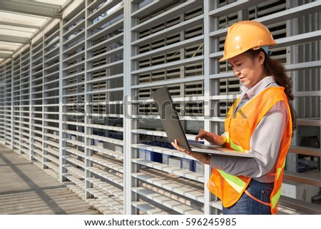 Female construction engineer working on laptop at site #596245985