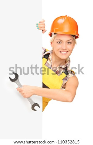 Female construction worker holding a wrench, standing behind white panel - stock photo