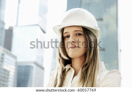 Female construction worker in hard hat on city background