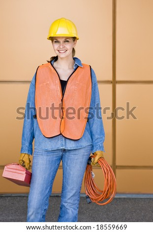 Female construction worker posing in hard-hat with toolbox and electric cord