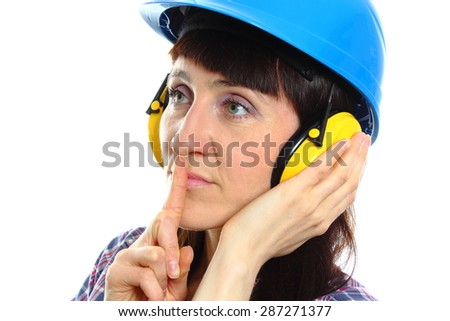 Female construction worker wearing protective helmet and headphones, holding index finger to lips and showing silence sign, safety at work and ear protection. White background #287271377