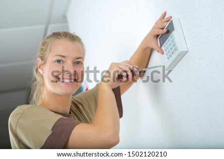 Female contractor fitting electronic keypad to wall #1502120210