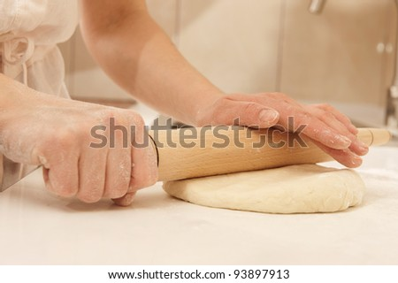 Female cook rolling dough with rolling-pin. Closeup view