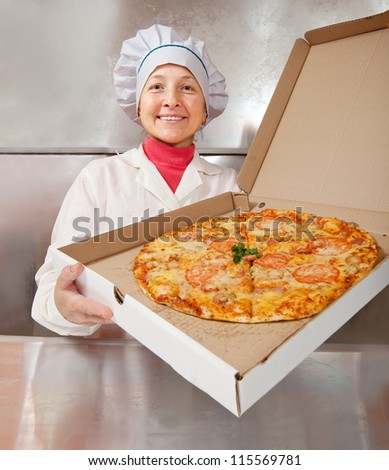 female cook with fresh  pizza in box at kitchen - stock photo