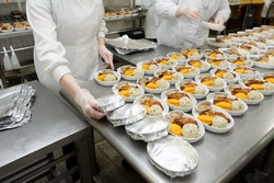 Female cooks are wrapping airline food in foil, commercial kitchen, reality shot