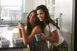 Female couple embracing in the kitchen look to camera