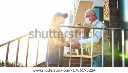 Female courier in medical mask and gloves bringing packet with fresh food to retired old man. Young Caucasian woman handing bag with grocery to male pensioner outdoor at house. Delivery service