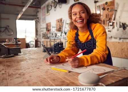 Female Craftsman In Carpentry Workshop For Bamboo Bicycles Using Digital Tablet And Smart Speaker Stock photo ©