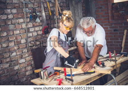 Female craftsman,in her workshop with her father,blonde with protective glasses and work suit - Shutterstock ID 668512801
