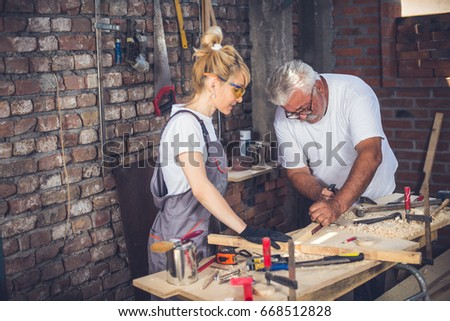 Female craftsman,in her workshop with her father,blonde with protective glasses and work suit - Shutterstock ID 668512828