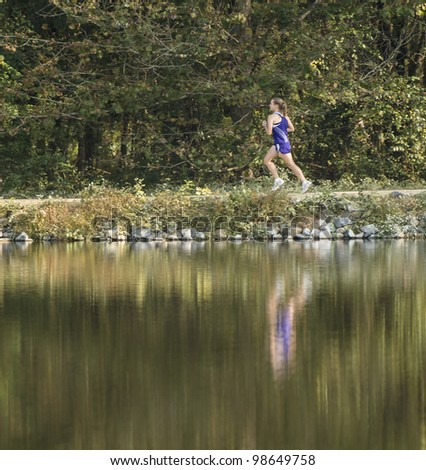 Female cross country runner with reflection in lake