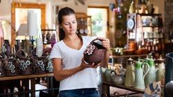 Female customer choosing handmade earthenware in modern pottery workshop