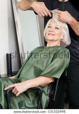 Female customer getting haircut in beauty salon