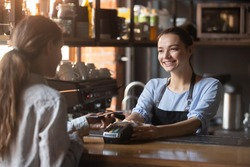 Female customer holding phone near nfc terminal make contactless mobile payment with smiling waitress barista saleswoman on coffeeshop counter, woman client pay in cafe with cellphone via pos machine