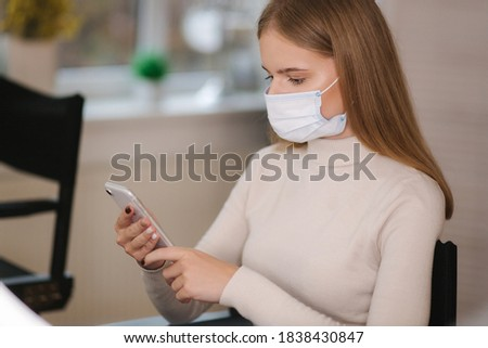 Female customer in beauty salon sitting in medical mask and use phone. Beautiful young blond hair woman wiating for brow master Zdjęcia stock ©