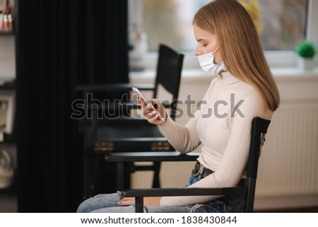 Female customer in beauty salon sitting on hight chair in medical mask and use phone. Beautiful young blond hair woman wiating for brow master. Open nose Zdjęcia stock ©