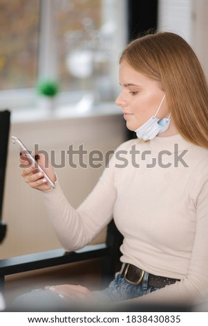 Female customer in beauty salon sitting on hight chair in medical mask on chin and use phone. Beautiful young blond hair woman wiating for brow master Zdjęcia stock ©