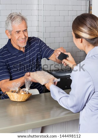 Female customer making credit card payment at cash counter while receiving product