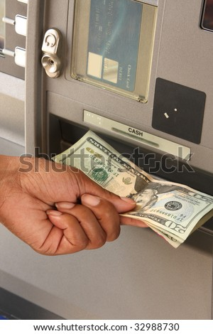 Female customer retrieving money from ATM