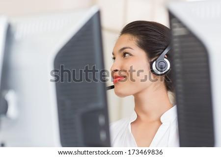 Female customer service representative working at computer in call center