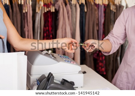 Female customer with shopping bag receiving credit card from saleswoman in boutique