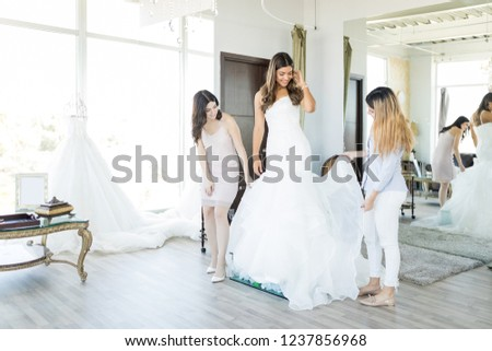 Female customers checking out dress worn by beautiful friend in bridal shop