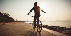 Female cyclist hands free cycling riding bike with arms outstretched in the coasts sunrise