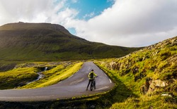 Female cyclist standing next to the bicycle on a mountain road.  Undefined young bicyclist girl with a backpack, helmet and yellow coat.  Faroe Islands mountain biking in a beautiful natural scenery