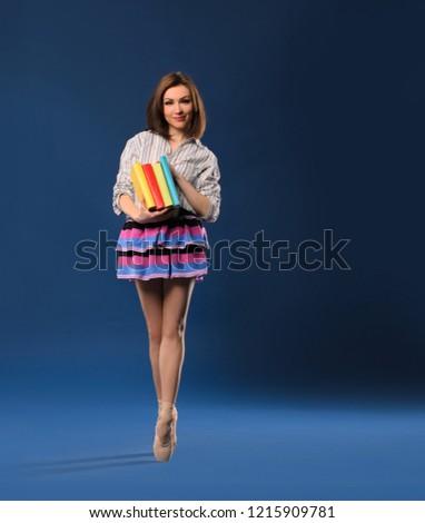female dancer in miniskirt on tiptoe with pile of books on dark blue studio background - Shutterstock ID 1215909781