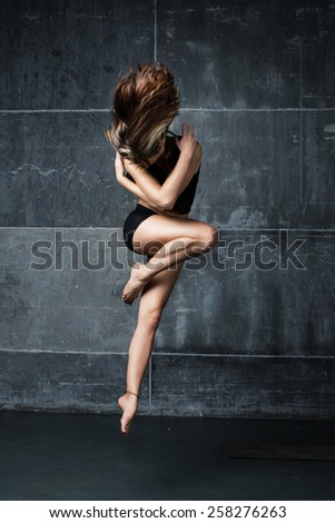 Female dancer jumping in contemporary dance in the studio