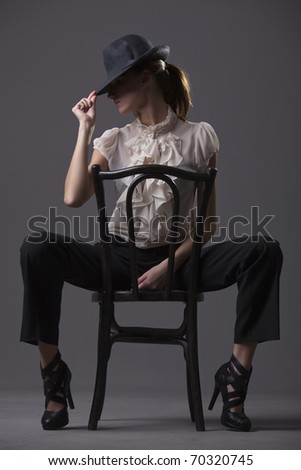 female dancer with hat sitting on the chair over grey background