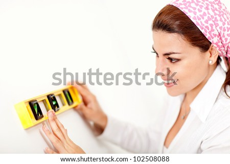 Female decorator holding a level instrument and smiling