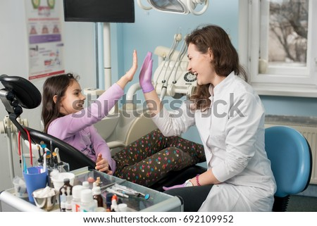 Female dentist and lovely kid after treating teeth at dental clinic office, smiling and giving high-five. Dentistry, medicine, stomatology and health care concept. Dental equipment