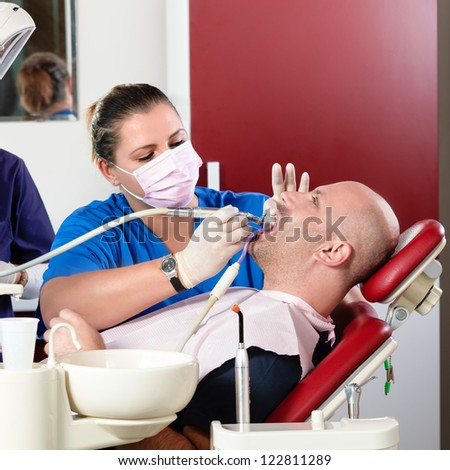 Female dentist doing a medical procedure to her patient