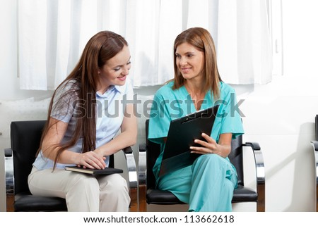 Female dentist showing something to young patient on clipboard in clinic