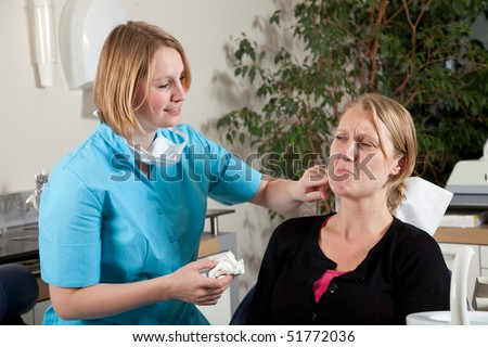 Female dentist touching the sore area on her patients cheek