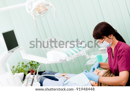 Female dentist with mask and gloves working on patient