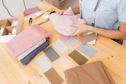 Female designer dressmaker Working on sewing machine in studio. Forms color palette for tailoring fashion clothes.