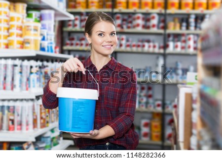 Female designer is holding paint for redecorate room in the store.